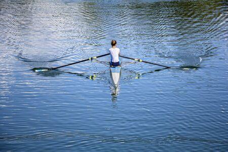 hilera: Mujeres Rower en un bote, remando en el lago tranquilo