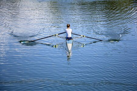 row: Women Rower in a boat, rowing on the tranquil lake