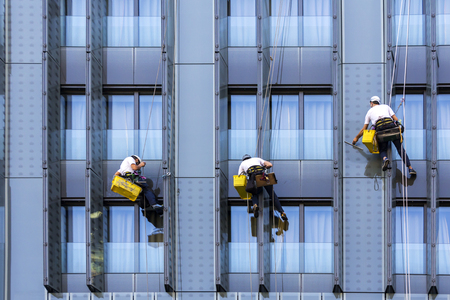 window repair: Three climbers wash windows and glass facade of the skyscraper Stock Photo