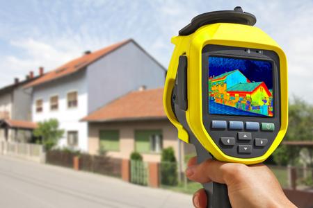 eficiencia: Grabación de pérdida de calor en la casa con la cámara infrarroja térmica Foto de archivo