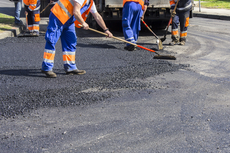 patching: Workers on Asphalting paver machine during Road street repairing works