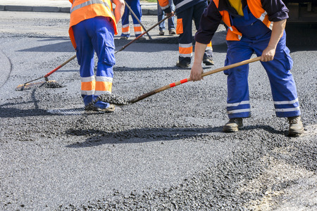 Workers on Asphalting paver machine during Road street repairing works