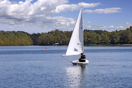 Small white boat sailing on the lake