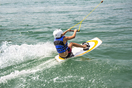 A young wakeboarder in action on the lake