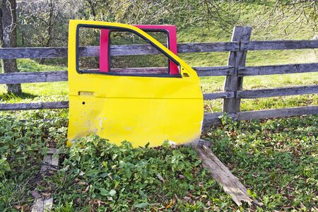 autos: Yellow and red Car doors wreck in the meadow