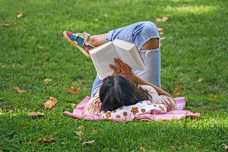 公園の芝生で寝転がって本を読む少女