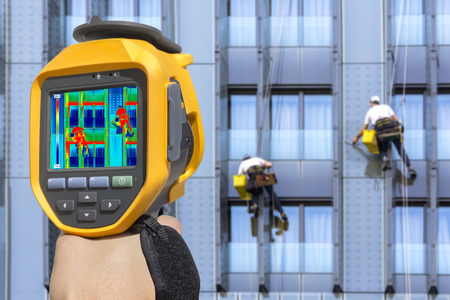 thermal image: Recording Two climbers wash windows With Thermal Camera Stock Photo