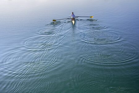 rower: Two Man in a boat, rowing on the tranquil lake Stock Photo