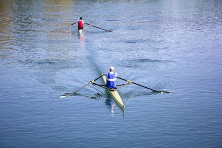 synchronous: Two Man in a boats, rowing on the tranquil lake
