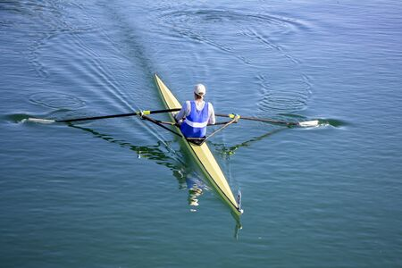 sculling: Young man Rower in a boat, rowing on the tranquil lake