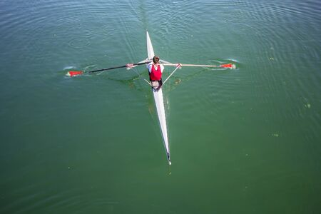 synchronous: Young man Rower in a boat, rowing on the tranquil lake