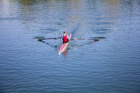 Young man Rower in a boat, rowing on the tranquil lake