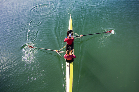 Two Man in a boat, rowing on the tranquil lake Stock Photo