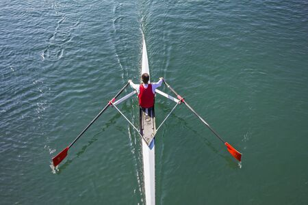 synchronous: Young Man in a boat trains rowing on the tranquil lake