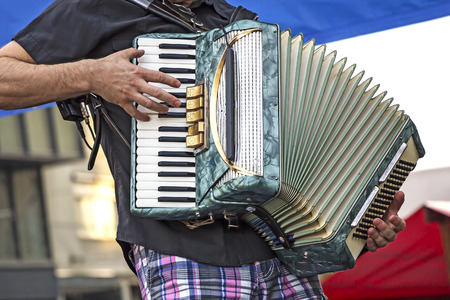 Young man musician playing the accordion