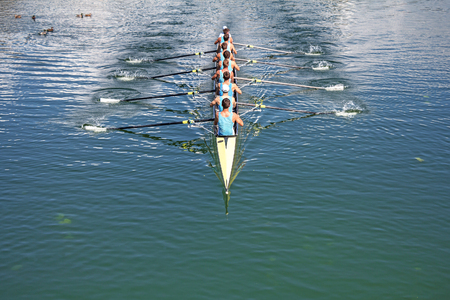 synchronous: Boat coxed eight Rowers training rowing on the lake