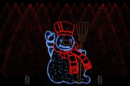 christmas atmosphere: Outdoor night shot of Illuminated christmas trees and Snowman for the perfect Christmas atmosphere