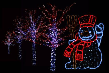 magical equipment: Outdoor night shot of Illuminated trees and Snowman for the perfect Christmas atmosphere