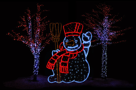 christmas atmosphere: Outdoor night shot of Illuminated trees and Snowman for the perfect Christmas atmosphere