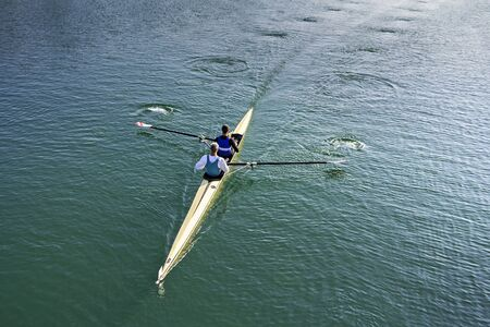 sculling: Two Man in a boat, rowing on the tranquil lake Stock Photo