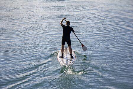 Ponte de pie hombre de la tarjeta de paleta paddleboarding en el lago tranquilo
