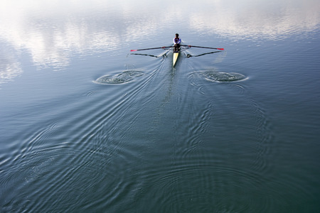 rower: Young man in a boat, rowing on the tranquil lake