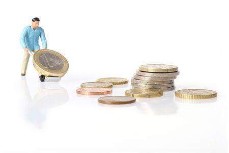 miniature: Miniature worker drives euro coins in wheelbarrow