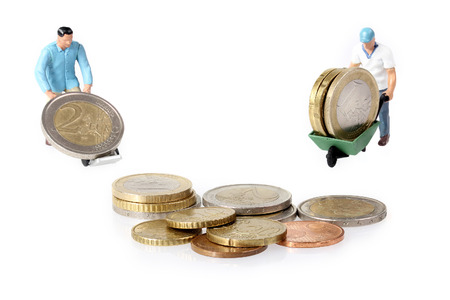 Twee Miniatuur arbeiders drijft euromunten in kruiwagen Stockfoto