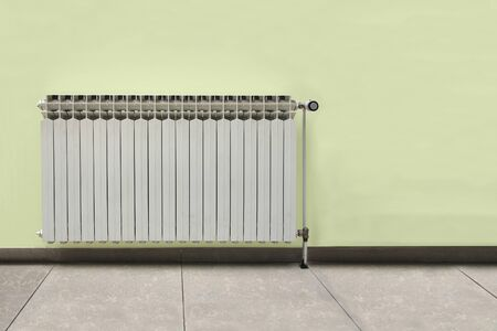optimal: Gray radiator on a yellow wall in an apartment