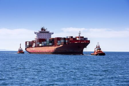 Tugboats pulling container cargo ship to harbor