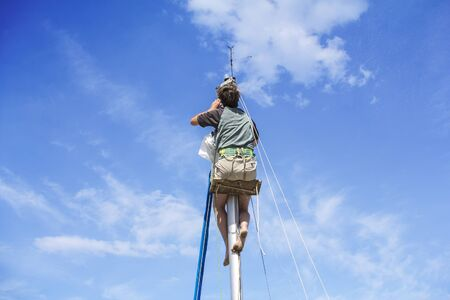 reparations: Young man hanging and repairs yacht mast