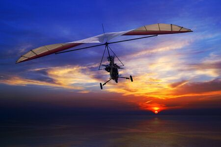 motor: The motorized hang glider in the sunset above sea Stock Photo