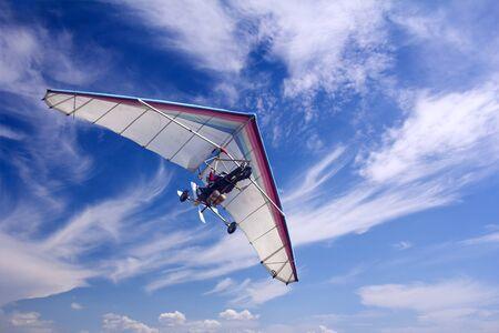 paraglide: Motorizedr paraglider flying in the blue sky