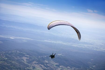 Paraglider flying over mountains to the valley