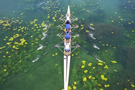 skiff: Four women rowing on the tranquil lake Stock Photo