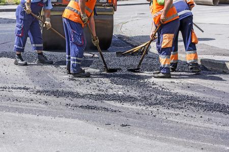 paver: Workers on Asphalting paver machine during Road street repairing works