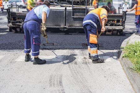 asphalting: Workers on Asphalting paver machine during Road street repairing works