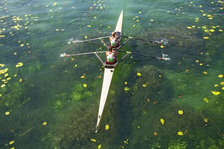 synchronous: Two rowers in a boat, rowing on the tranquil lake