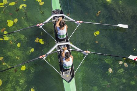 Two rowers in a boat, rowing on the tranquil lake