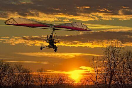 Der Motorsegler fliegen in den Sonnenuntergang hängen Standard-Bild