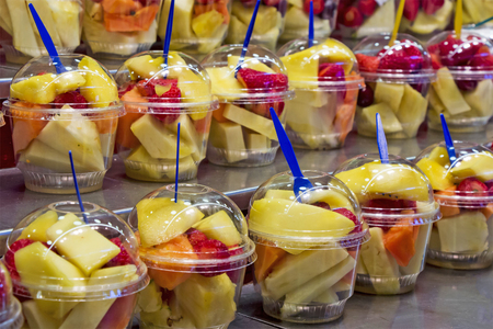 filled: Fresh Fruit cocktail salad in plastic cups on a market stall Stock Photo