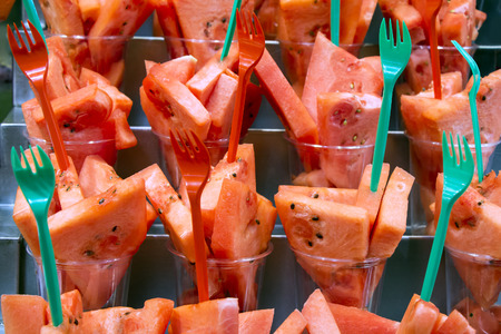 Fresh Watermelon cocktail salad in plastic cups on a market stall