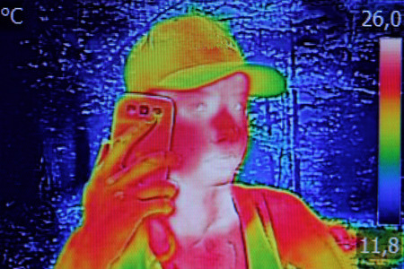thermography: Infrared thermography image showing the heat emission when Young girl used smartphone or cell phone