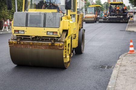 asphalting: Compactor roller during road construction at asphalting work