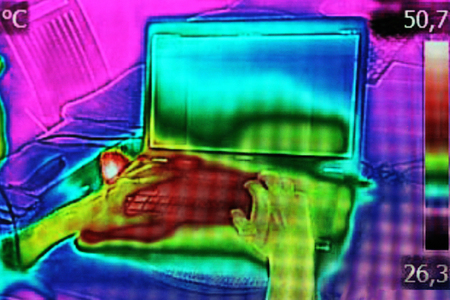 thermography: Infrared thermography image showing the heat emission when woman used notebook Stock Photo