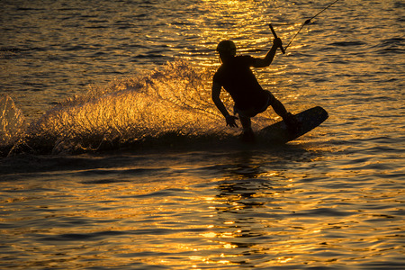 kiteboarding: Silhouette Wakeboarder in action on sunset Stock Photo