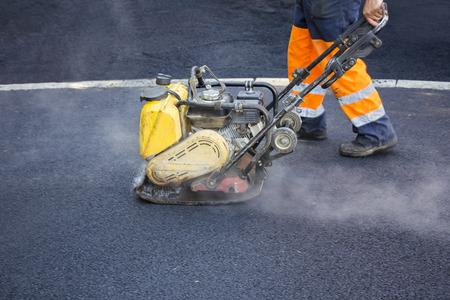 vibration machine: Worker use vibratory plate compactor compacting asphalt at road repair