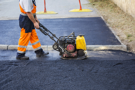 Worker use vibratory plate compactor compacting asphalt at road repair