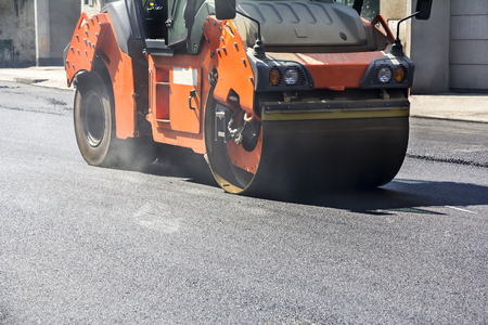 compacting: Roller compactor working on the new road construction site