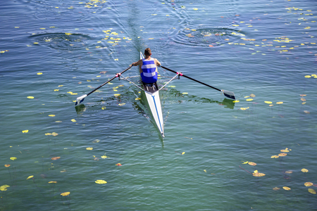 paddles: A Young single scull rowing competitor paddles on the tranquil lake